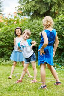 Mädchen spielen ein Hüpfspiel im Garten