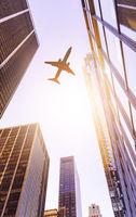 plane over modern office buildings