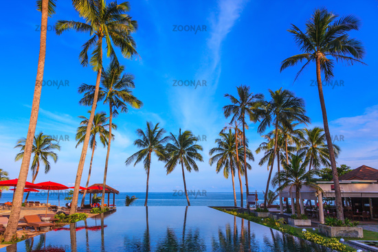 Rest of the Andaman Sea. Popular resort on the island of Koh Samui. Pool surrounded by palm trees on the sea beach. On the edge of the pool red sun canopy