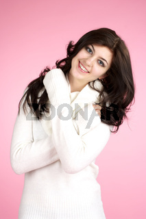 Young cheerful woman with white sweater over pink background