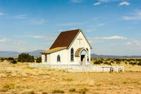 Old-fashioned white church in the country surrounded by open fields.