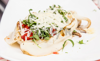 Cuttlefish with tomato, salad and Parmigiano cheese