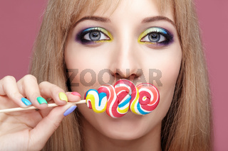 Beauty portrait of young blonde woman on pink background. Female with candy lollipop on stick in hands.