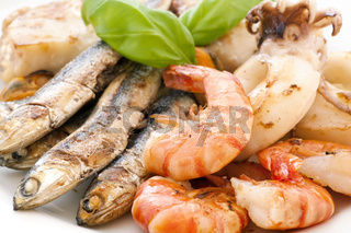 Fried seafood with anchovies and fish as closeup on a white plate