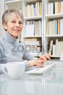 Ältere Geschäftsfrau schreibt am Computer