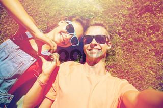 happy teenage couple taking selfie on summer grass