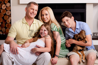 Lovable family poisng in living room as young boy holds little puppy in his arms