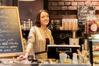 happy woman or barmaid at cafe counter