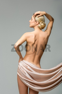 beautiful naked woman with silk fabrics covering intimate zone