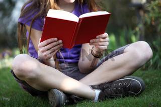 Kind im Garten liest ein Buch
