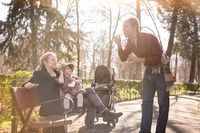 Young family with cheerful child in the park.