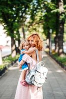 Woman hugs her daughter, holding her in her arms