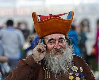 Älterer Mann mit Bart, Kappe und Orden telefoniert mit einem Mobiltelefon, Ulanbator, Mongolei