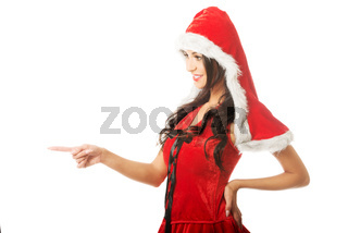 Portrait of beautiful woman wearing santa clothes and pointing to the left