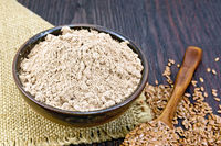 Flour linen in bowl with seeds in spoon on sacking
