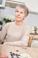 Frau als Rentner mit Brettspiel