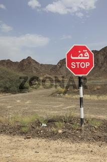 zweisprachiges STOP Schild in der Wüste im Oman