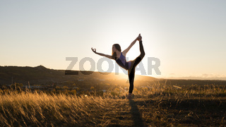 Woman doing yoga dancers pose during sunset