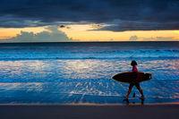 Woman surfer at sunset. Bali
