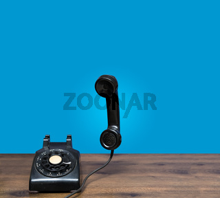 Old rotary dial telephone on wooden desk with copy space