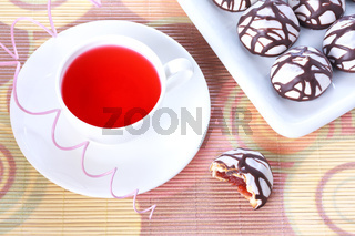 Cup of red tea and chocolate decorated iced spice cakes on bamboo mat
