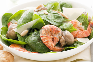 Fried shrimp with spinach and mushrooms as closeup on a white plate.