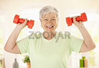 Energetic senior woman with dumbbels