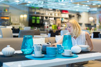 Woman choosing the right decor for her apartment in a modern home furnishings store.