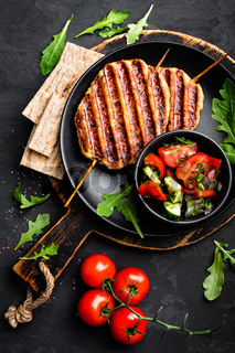 Juicy grilled chicken meat lula kebab on skewers with fresh vegetable salad on black background, top view