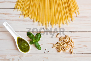 Pesto genovese sauce and linguine pasta, pine nuts and garlic on a table
