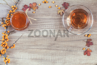 Autumn healthy hot drink concept. Branch of common sea buckthorn with berry, cup of tea, jar of jam on light wooden background. Toned photo with copy space.