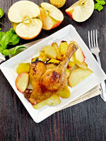 Duck leg with apple and basil in plate on dark board top