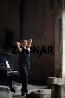 fashion girl in black dress in grunge interior with the piano