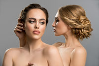 Two models topless embracing tenderly in studio