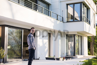 man in front of his luxury home villa