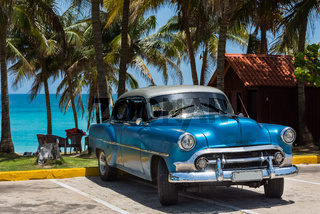Amerikanischer blauer Chevrolet Oldtimer parkt am Strand unter Palmen in Varadero Cuba - Serie Cuba Reportage