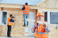 Handwerker bauen Holzhaus als Ferienhaus