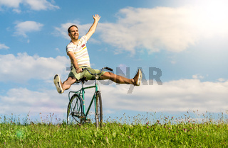 Happy winning man on bicycle. Legs and arms raised up.