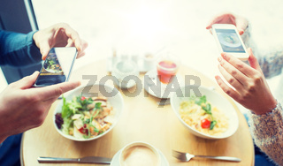 close up of couple picturing food by smartphone