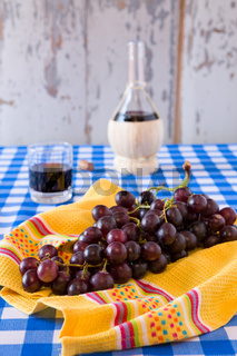 Bunch of red grapes and a glass of red wine with a wine flask