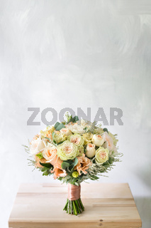 floral composition with roses and mix flowers in glass vase on a gray background.