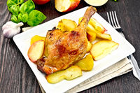 Duck leg with apple and basil in plate on dark board