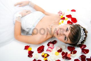Beautiful  bride on  floor among red rose petals