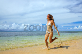 Young woman running on the beach on Taveuni Island, Fiji.