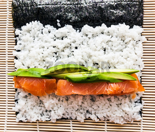 Preparing sushi background. Salmon, avocado, rice on seaweed.