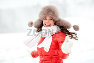 happy woman in winter fur hat outdoors