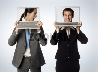 A male and female with swapped heads on their laptops