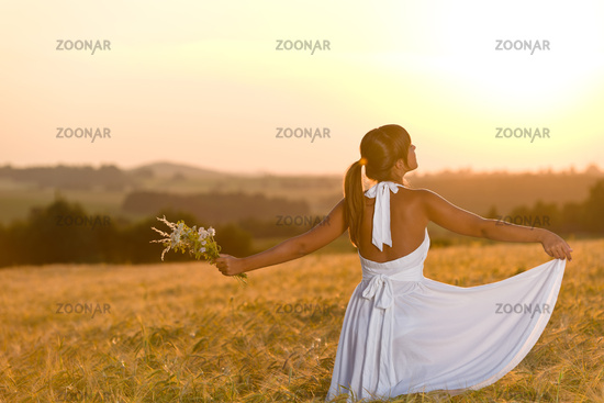 Romantic woman in sunset corn field wear dress