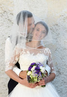 Happy young couple with bridal bouquet