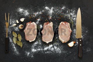 Three slices of raw meat, Raw, T-bone Steak, fresh herbs, SALT, garlic, onion, pepper on a dark stone background, top view, space for text, closeup